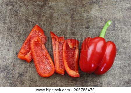 fresh red bell pepper (capsicum) and some cut pieces on  a grungy metal background
