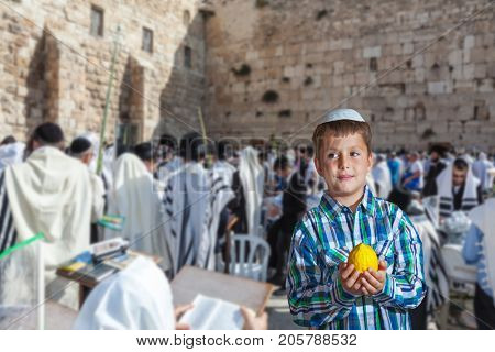 The greatest shrine of Judaism is the Western Wall of the Temple. Autumn Jewish holiday Sukkot. Beautiful Jewish boy in white skullcap, with etrog