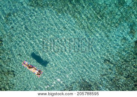 aerial view of a beautiful young woman in bikini on a matress in the sea