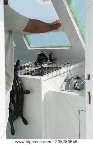 The captain controls the yacht. Sea adventures.