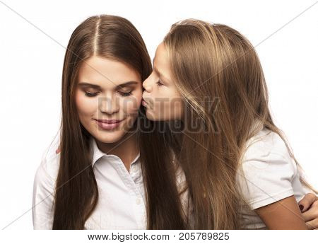 Gentle kiss of the younger sister, isolated on white background