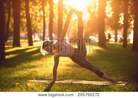 Beautiful sporty fit yogini woman practices yoga advanced side plank pose vasisthasana in the park at sunset