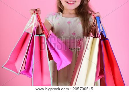 Lady shopper in dress with wavy hair. Girl holds shopping bags on pink background close up. Schoolgirl with red pink and yellow packets does shopping. Shopaholic and childhood concept