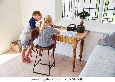 Boy And Girl In Bedroom With Digital Tablet Doing Homework