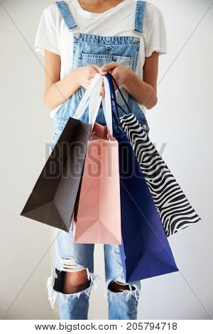 Close Up Of Woman Standing At Home Holding Shopping Bags