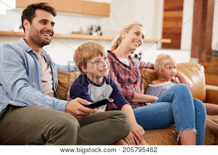Family Sitting On Sofa In Open Plan Lounge Watching Television