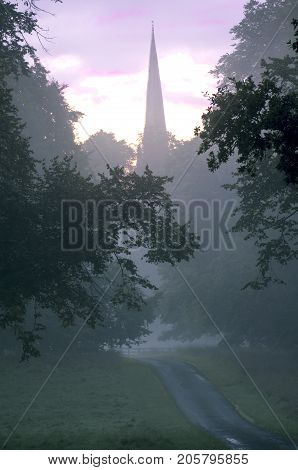 Village Church in Morning Mist Early morning view of a village church through an avenue of trees in morning mist