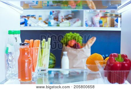 Open refrigerator with fresh fruits and vegetable
