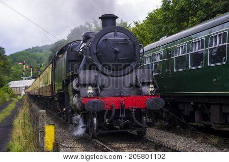 Standard 4 Tank Engine  Standard 4 tank Engine hauling a passenger train passing a stationary Class 101 DMU.