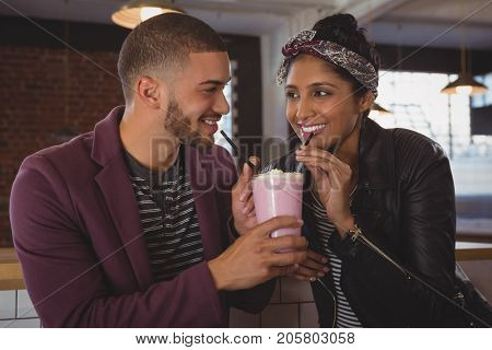 Happy young friends enjoying milkshake at counter in cafe
