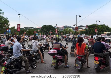 Guilin China - July 31 2012: Large group of motorcycles in a traffic jam in a cross road in the city of Guilin in China