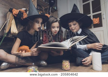 An ancient book of spells. Children dressed in costumes of monsters for Halloween are sitting on the floor and are looking at the book of spells with interest