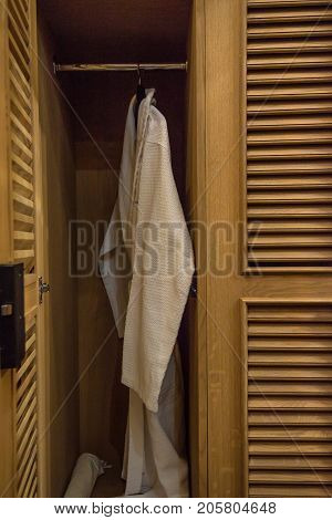 Close up white bath robe hanging in open closet in hotel