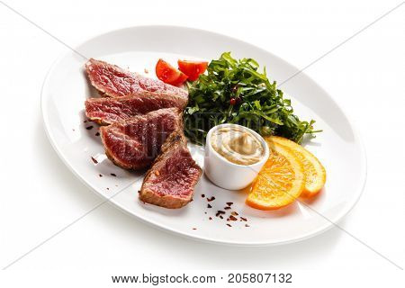 Fillet mignon - grilled beefsteaks with vegetables on white background