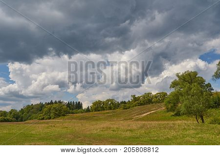Landscape with thunder clouds sky. Natural summer background