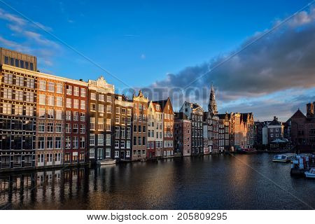 Houses and tourist boats on Amsterdam canal pier Damrak on sumset. Amsterdam, Netherlands