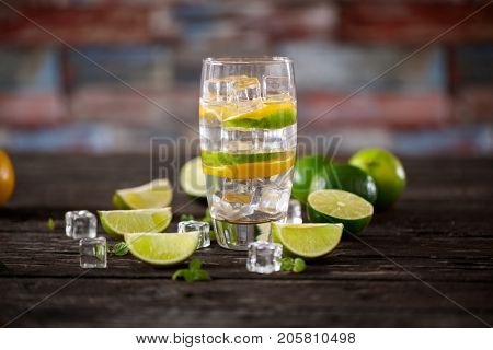 Fresh cocktail with soda water, ice, lime, orange and mint on wooden table