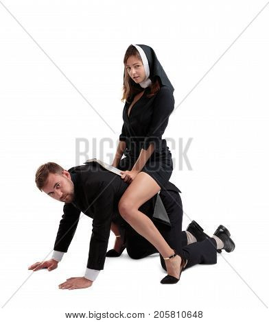 Man and sexy woman playing in games in a black suits. Religion concept.The nun and the priest sin.