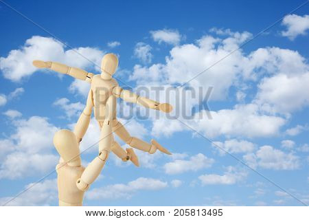 Wooden figures of parent carring his child over his head on sky background, collage