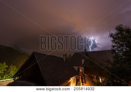 Flash during a thunderstorm at night behind a farming house in the Austrian alps