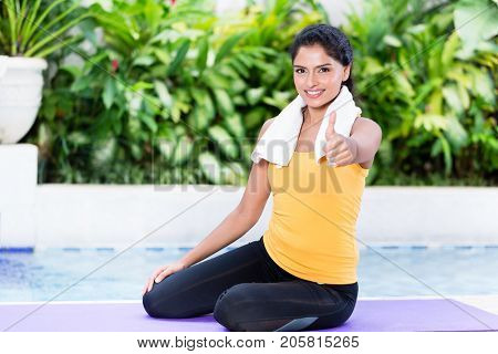 Fit young woman showing thumb up during workout routine on exercise mat outdoors