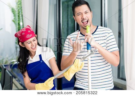 Indonesian couple having fun cleaning the home, woman and man playing air guitar on duster and broom