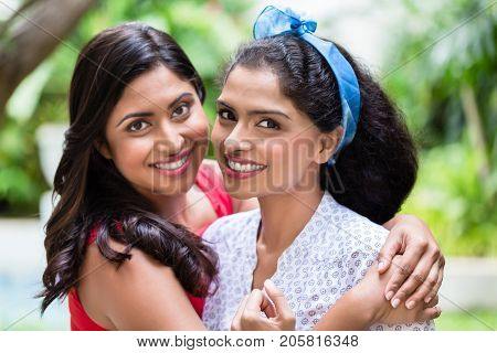 Close-up portrait of two young women posing together as best friends outdoors