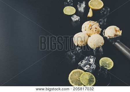 Ice cream scoops with ice cubes and lemon slices and scoop on black background. Delicious cold sweet dessert, top view, copy space