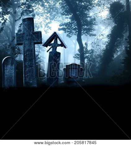 Medieval stone crosses and tombstones in a cemetery in a misty forest. Photo toned in blue color. Copy space for your text
