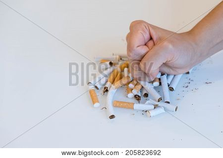 Stop Smoking. Close Up Of Male Hand Breaking Cigarettes With His Fist. Isolated And Copy Space In Le