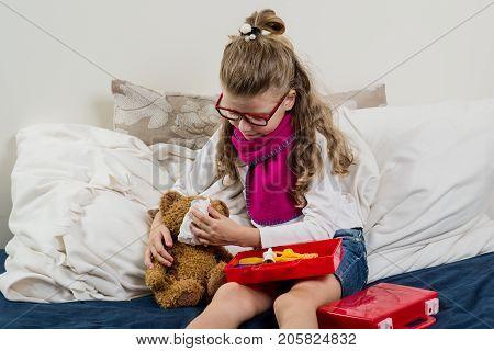 Sick child girl in glasses heals his sick Teddy bear