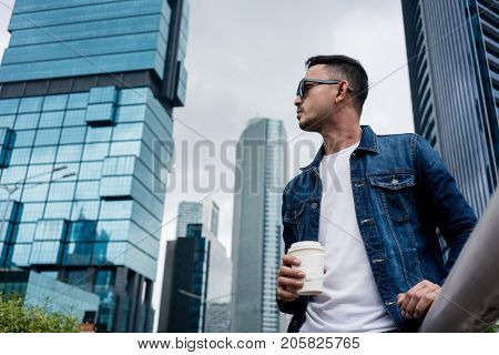 Low angle view portrait of a young man wearing sunglasses and blue denim jacket while daydreaming outdoors in a modern city