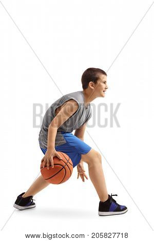 Profile shot of a boy dribbling a basketball isolated on white background
