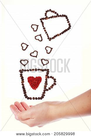 Coffee mug full of coffee beans with heart shapes