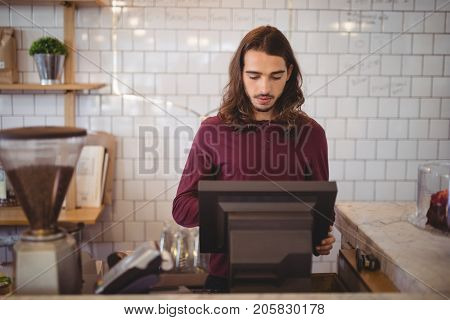 Young waiter with long hair using cash register against wall at coffee shop