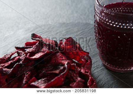 Close-up of beetroot with juice glass on plate over slate