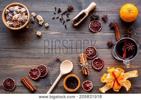 Merry christmas in winter evening with warm drink. Hot mulled wine or grog with fruits and spices on wooden desk background top view