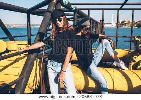 Two model wearing plain black t-shirt and hipster sunglasses, teen urban clothing style, mockup for tshirt print store