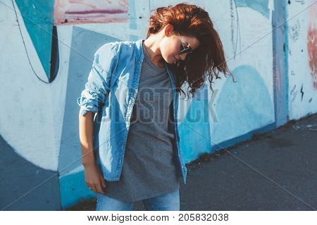 Model wearing plain gray tshirt, denim shirt and hipster sunglasses posing against street wall, teen urban clothing style