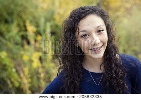 Beautiful Hispanic teen girl outdoor portrait. Cute and smiling with a mouth full of braces and face covered in freckles