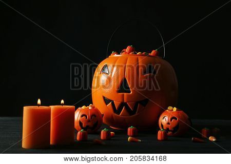 Halloween Candy Corns In Baskets With Candles On Wooden Table