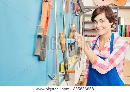 Woman as carpenter trainee or apprentice at workshop