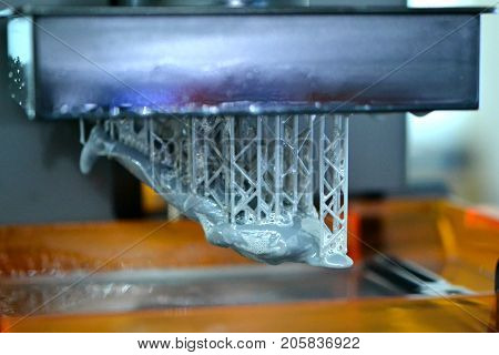 Stereolithography DPL 3d printer create detail and liquid drips, platform slowly move with liquid close-up. Progressive modern additive technology 3D printing, create scaled model by UV polymerization
