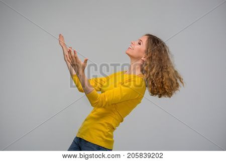beautiful curly young woman in yellow clothes holds hands up speaking thank you on gray background