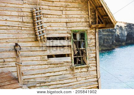 Abandoned old wooden board house ruin next to sea shore