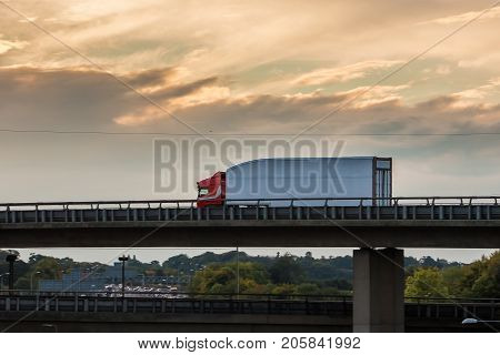 Lorry in motion on the viaduct during sunset.