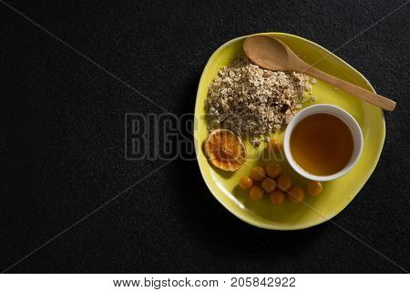 Overhead of dried orange slice, oatmeal, golden berry and maple syrup in plate