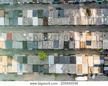 Dilapidated old shack looking one story buildings sitting in shade, depressed area, poverty, topview