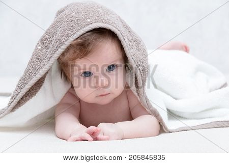 Cute newborn baby girl with beautiful blue eyes on a white terry coverlet. Adorable baby looking out under a white blanket or towel. Sad baby girl in white towel after shower