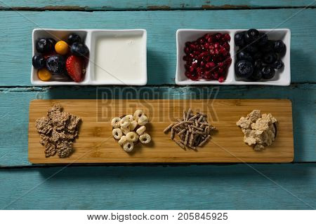 Assortment of breakfast cereals, yogurt and fruits on wooden table